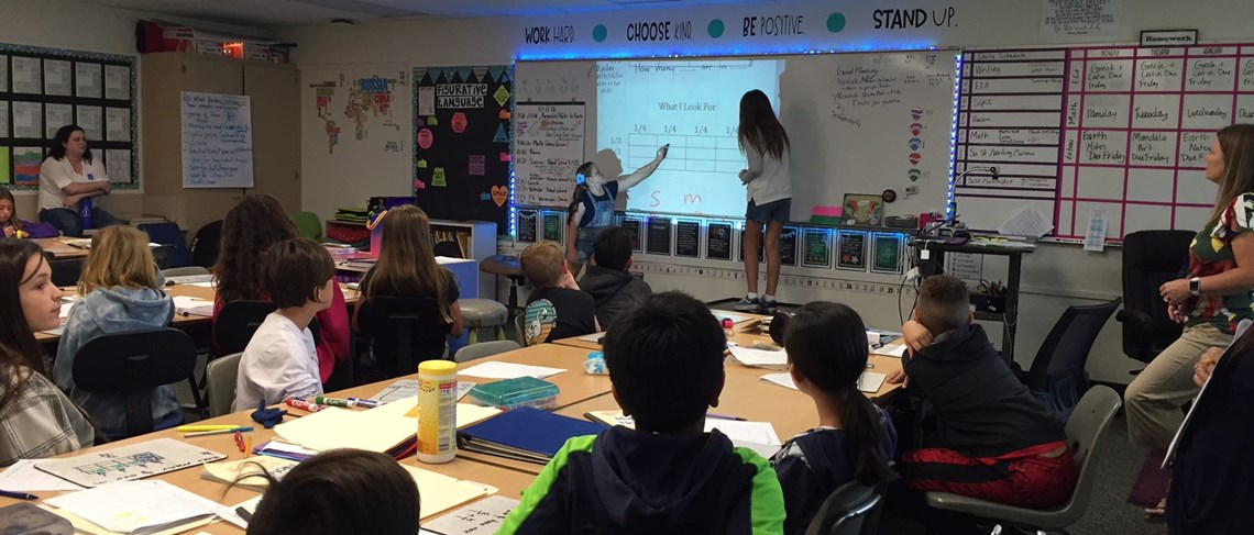 Students demonstrate solving a math problem